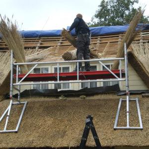 Rietdekker op het dak van een boerderij in Niuewleusen